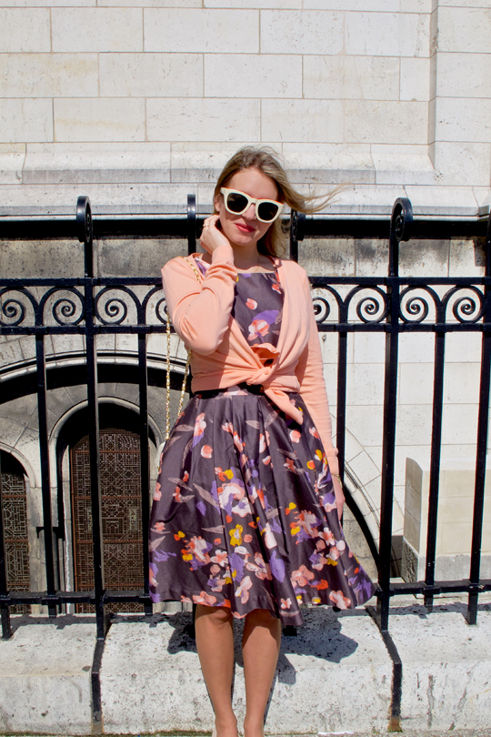 Blonde fashion and style blogger girl standing in front of Sacré-Cœur in Paris, wearing a flower dress, cardigan, sunglasses and a Chanel bag