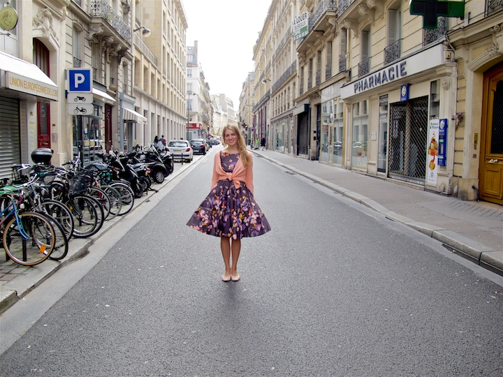 Smiling blond fashion and style blogger girl standing in the streets of Paris, wearing a flower dress, cardigan and ballet flats