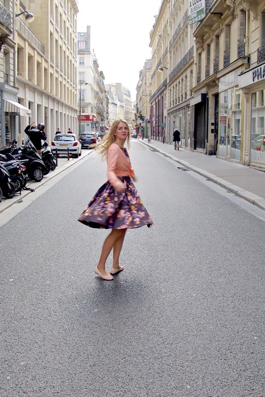 Blonde fashion and style blogger girl dancing in the streets of Paris, wearing a flower dress, cardigan and ballet flats