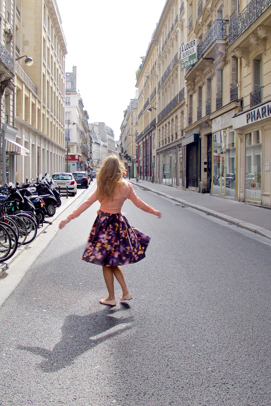 Blond fashion and style blogger girl dancing in the streets of Paris, wearing a flower dress, cardigan and ballet flats