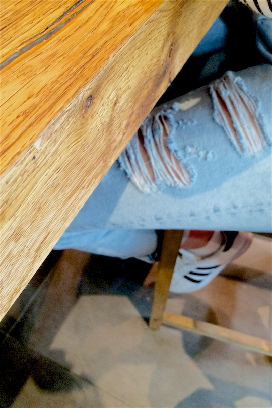 Bird's eye view of a fashion and style blogger girl's destroyed jeans and adidas sneakers