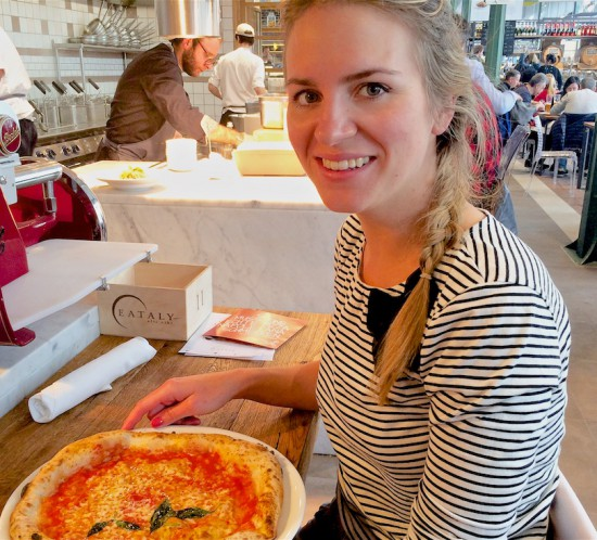 Smiling blonde fashion and style blogger girl with braided hair in closeup view eating pizza, wearing a striped top with bow
