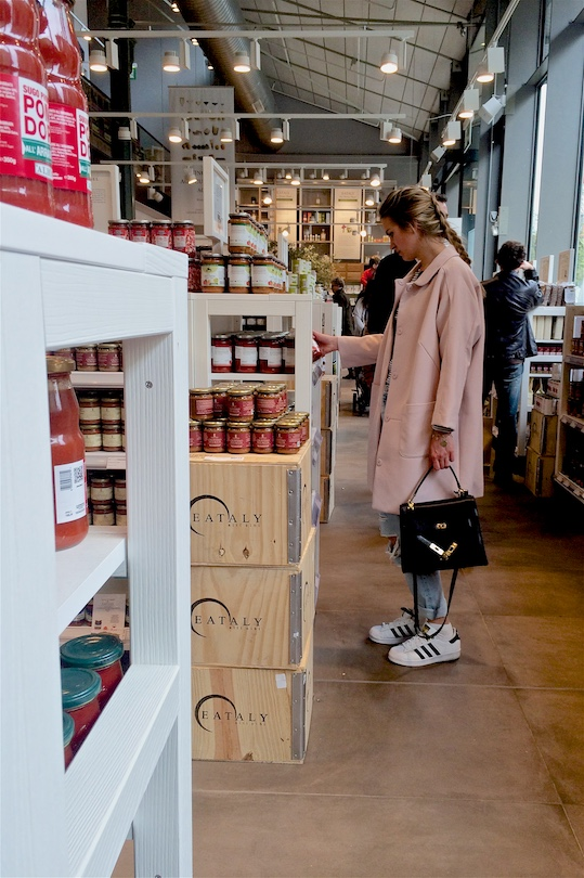 Blond fashion and style blogger girl with braided hair shopping at Eataly, wearing a striped top with bow, destroyed jeans, adidas sneakers, pink coat and a MCM bag