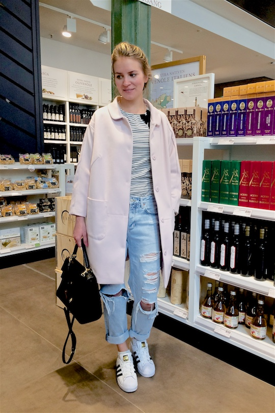 Smiling blonde fashion and style blogger girl with braided hair shopping at Eataly, wearing a striped top with bow, destroyed jeans, adidas sneakers, pink coat and a MCM bag