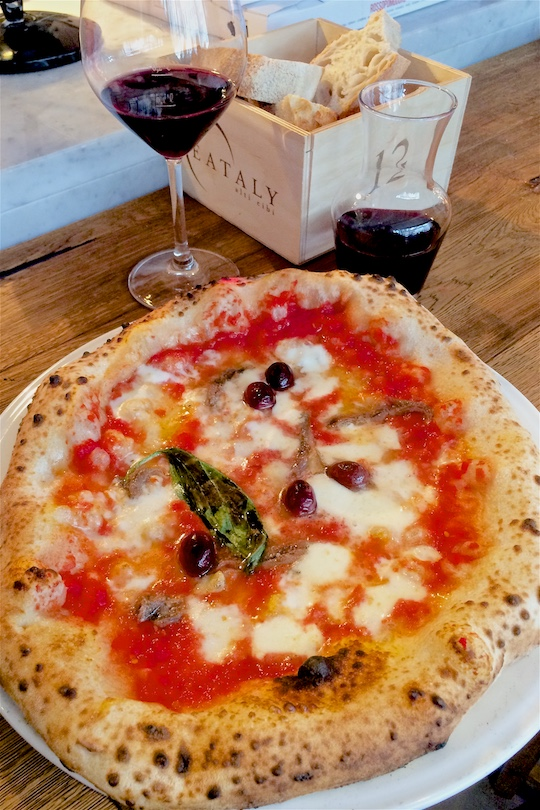 Delicious pizza Napoletana and a glass of red wine at Eataly