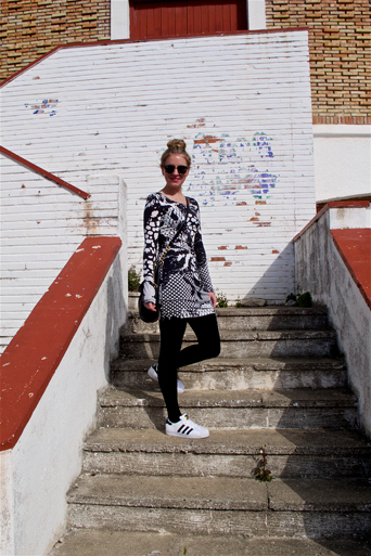 Blond fashion and style blogger girl walking up stairs, wearing a lace dress, Michael Kors bag, Rayban sunglasses and adidas sneakers