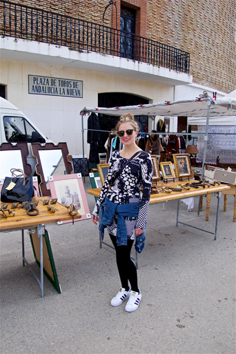 Blond fashion and style blogger girl at the weekly market called Rastro in Spain, wearing a lace dress, denim jacket, Michael Kors bag, Rayban sunglasses and adidas sneakers