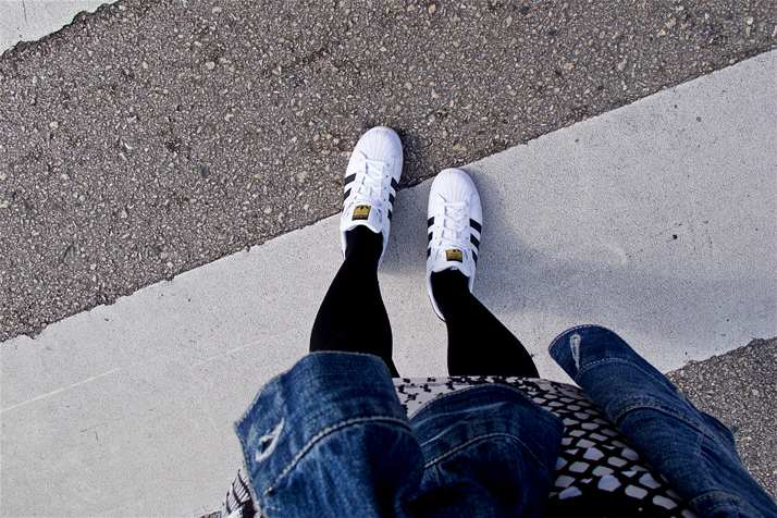 Bird's eye view of a fashion and style blogger girl's adidas sneakers, lace dress and denim jacket