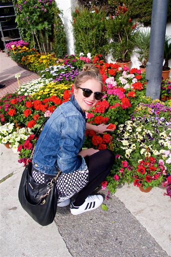 Blond fashion and style blogger girl shopping some flowers at the weekly market, wearing a lace dress, denim jacket, Michael Kors bag, Rayban sunglasses and adidas sneakers