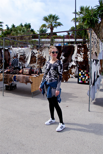 Blonde fashion and style blogger girl at the weekly market called Rastro in Spain, wearing a lace dress, denim jacket, Michael Kors bag, Rayban sunglasses and adidas sneakers