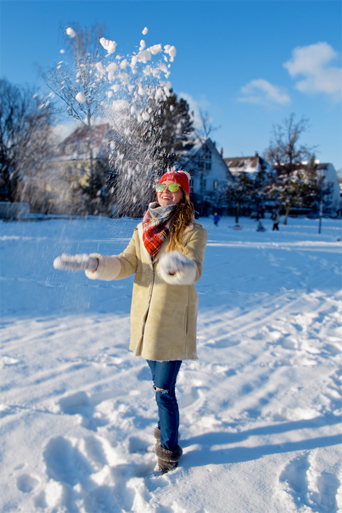 Smiling fashion and style blogger girl with sunglasses, orange beanie, plaid scarf and oversized winter coat throwing snow in the air in a snowy neighborhood