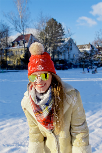 Smiling fashion and style blogger girl with sunglasses, orange beanie, plaid scarf and oversized winter coat with snow in her face in a beautiful, snowy scenery