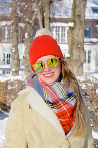 Smiling fashion and style blogger girl with sunglasses, orange beanie, plaid scarf and oversized winter coat in a snowy neighborhood