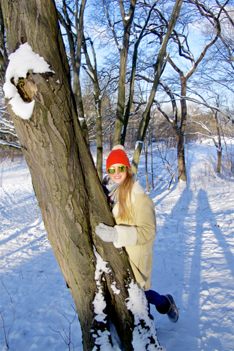Smiling fashion and style blogger girl with sunglasses, orange beanie, plaid scarf and oversized winter coat leaning on a tree in a snowy scenery