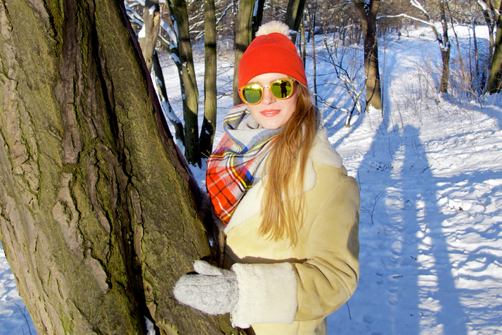 Fashion and style blogger girl with sunglasses, orange beanie, plaid scarf and oversized winter coat leaning on a tree in a snowy scenery