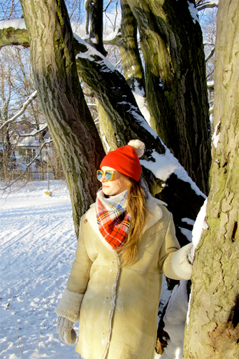 Fashion and style blogger girl with sunglasses, orange beanie, plaid scarf and oversized winter coat in a beautiful, snowy scenery
