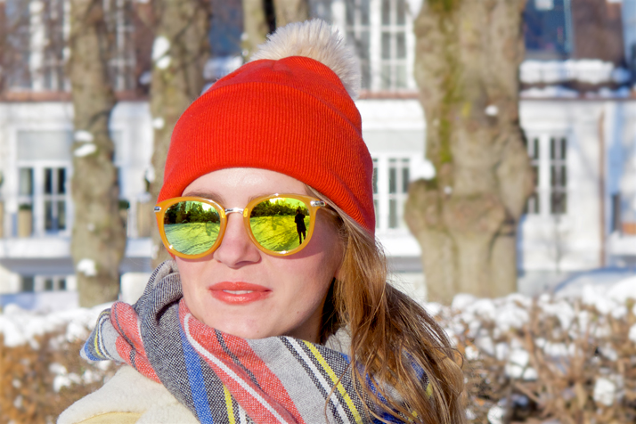 Fashion and style blogger girl in closeup view with sunglasses, orange beanie, plaid scarf and oversized winter coat in a snowy neighborhood