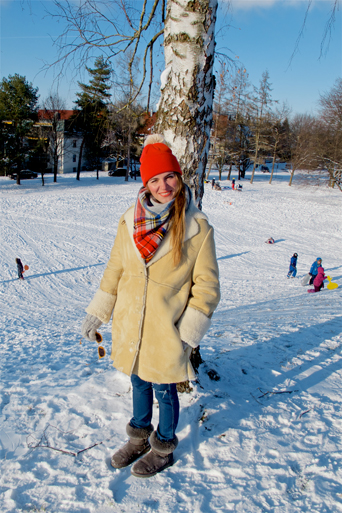 Smiling fashion and style blogger girl with orange beanie, plaid scarf and oversized winter coat in a snowy neighborhood