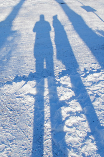 Shadows of fashion and style blogger girl and photographer on snow