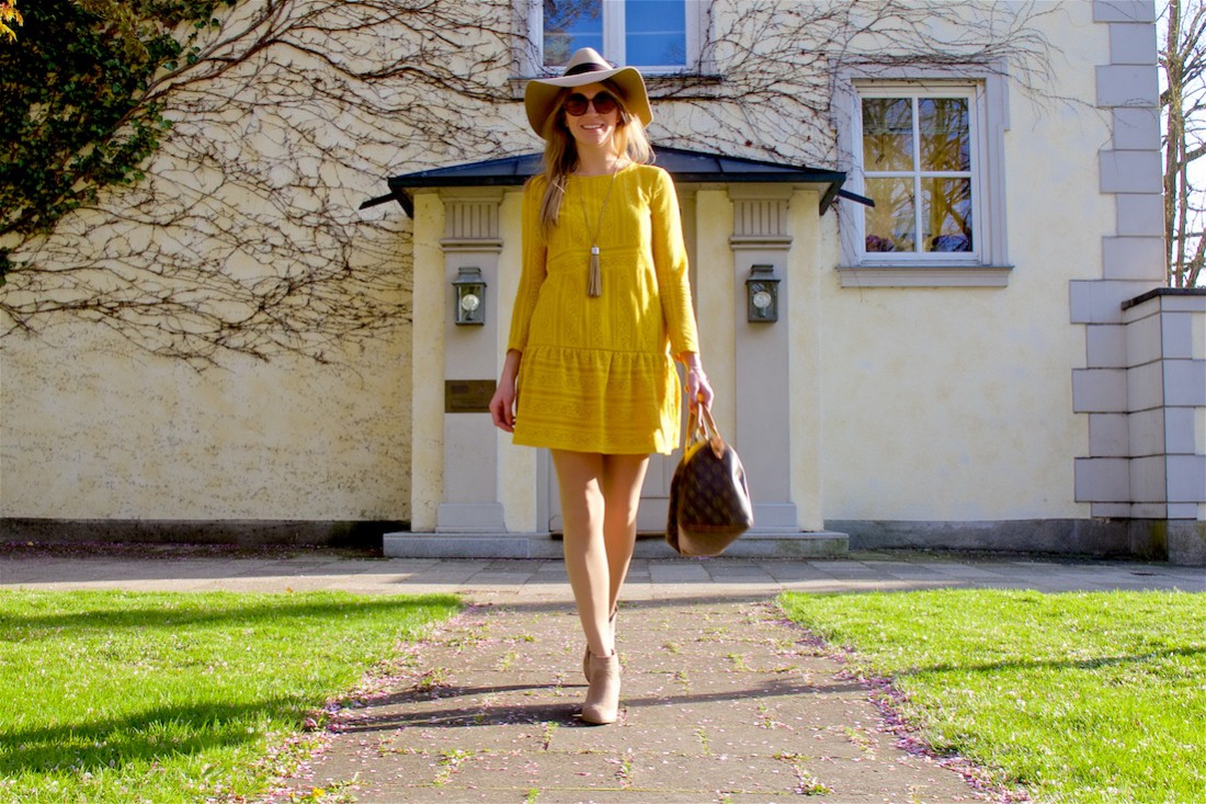 Smiling blonde fashion and style blogger girl wearing a yellow lace dress, sunglasses, floppy hat, fringe necklace, boots and a classic Louis Vuitton Monogram bag