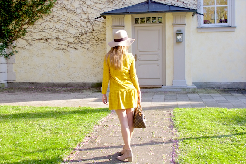 Blond fashion and style blogger girl wearing a yellow lace dress, floppy hat, boots and a classic Louis Vuitton Monogram bag