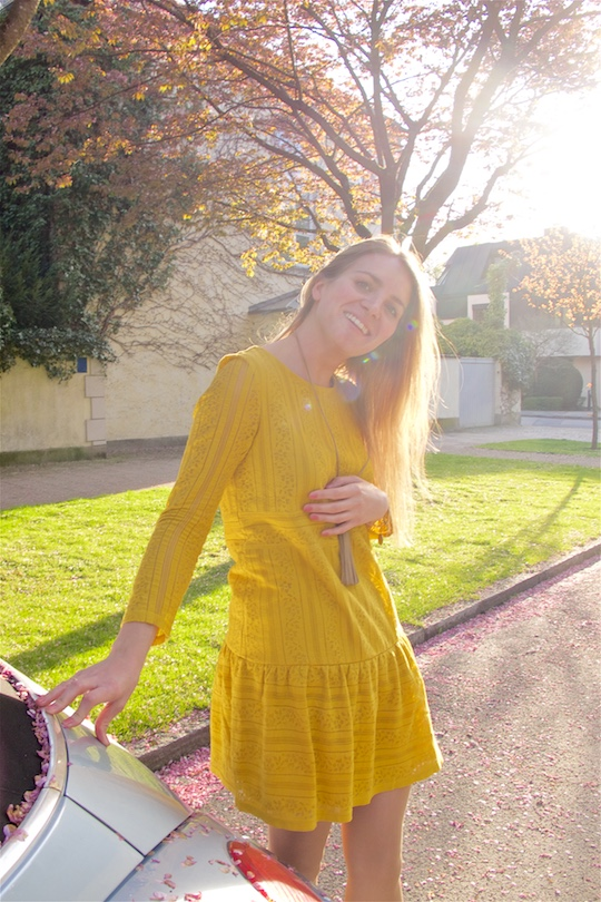 Smiling blond fashion and style blogger girl wearing a yellow lace dress and a fringe necklace