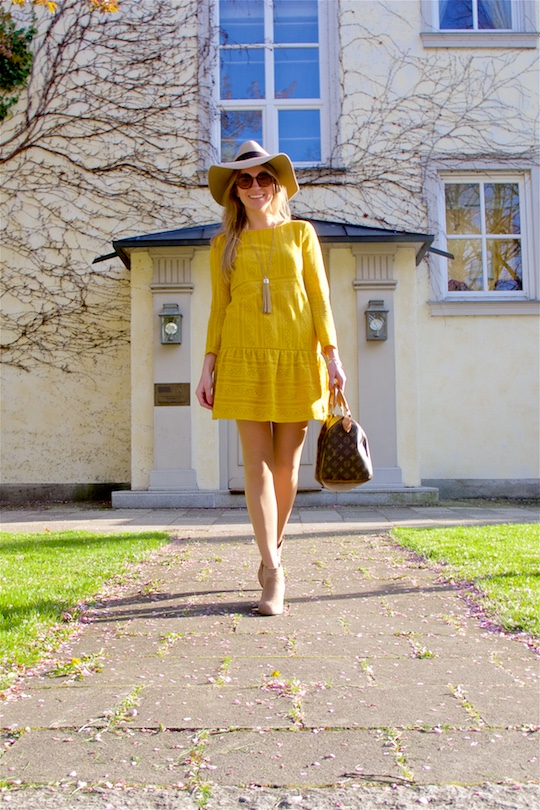 Smiling blond fashion and style blogger girl wearing a yellow lace dress, sunglasses, floppy hat, fringe necklace, boots and a classic Louis Vuitton Monogram bag
