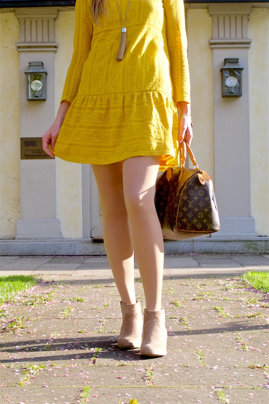 Fashion and style blogger girl in closeup view, wearing a yellow lace dress, fringe necklace, boots and a classic Louis Vuitton Monogram bag