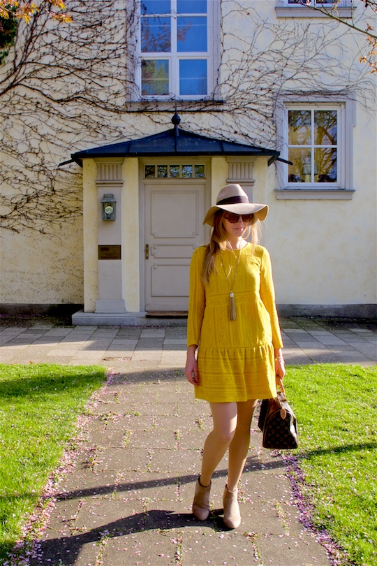 Blond fashion and style blogger girl wearing a yellow lace dress, sunglasses, floppy hat, fringe necklace, boots and a classic Louis Vuitton Monogram bag