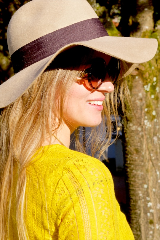 Smiling blonde fashion and style blogger girl in closeup view, wearing a yellow lace dress, sunglasses and a floppy hat