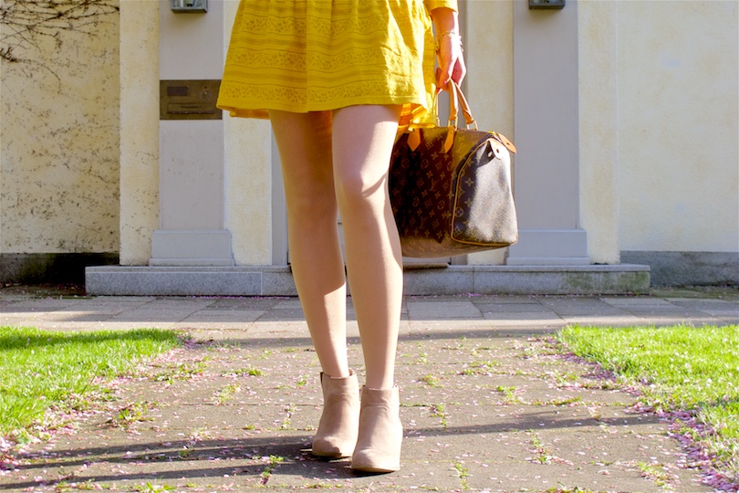 Fashion and style blogger girl in closeup view, wearing a yellow lace dress, boots and a classic Louis Vuitton Monogram bag