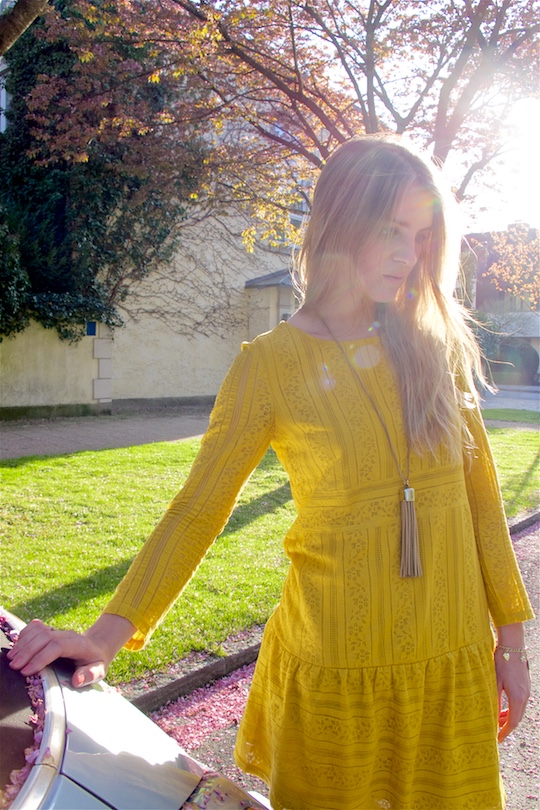 Blond fashion and style blogger girl wearing a yellow lace dress and a fringe necklace