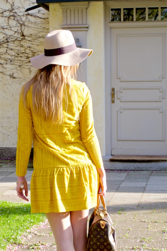 Blonde fashion and style blogger girl wearing a yellow lace dress, floppy hat and a classic Louis Vuitton Monogram bag