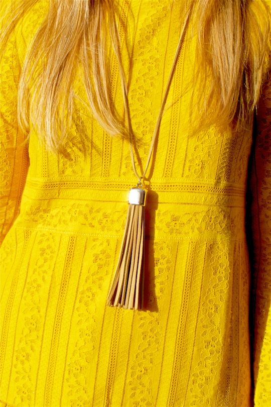Fashion and style blogger girl in closeup view, wearing a yellow lace dress and a fringe necklace