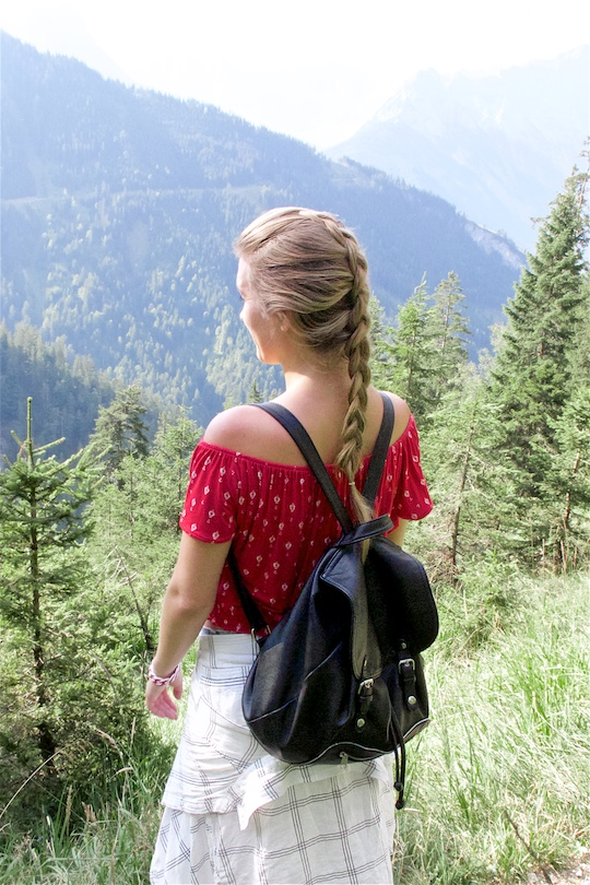 Hiking Day. Fashion and Style Blog Girl from Heartfelt Hunt. Girl with blonde dutch braid wearing a red off-shoulder top, plaid shirt, denim shorts, hiking boots and backpack.
