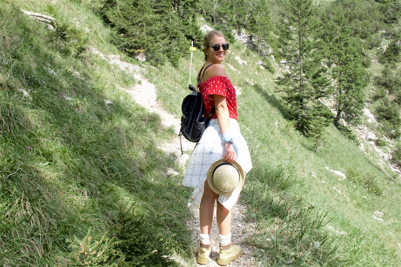 Hiking Day. Fashion Blogger Girl by Style Blog Heartfelt Hunt. Girl with blond dutch braid wearing a red off-shoulder top, plaid shirt, denim shorts, hiking boots, straw hat, backpack and Ray-Ban sunglasses.