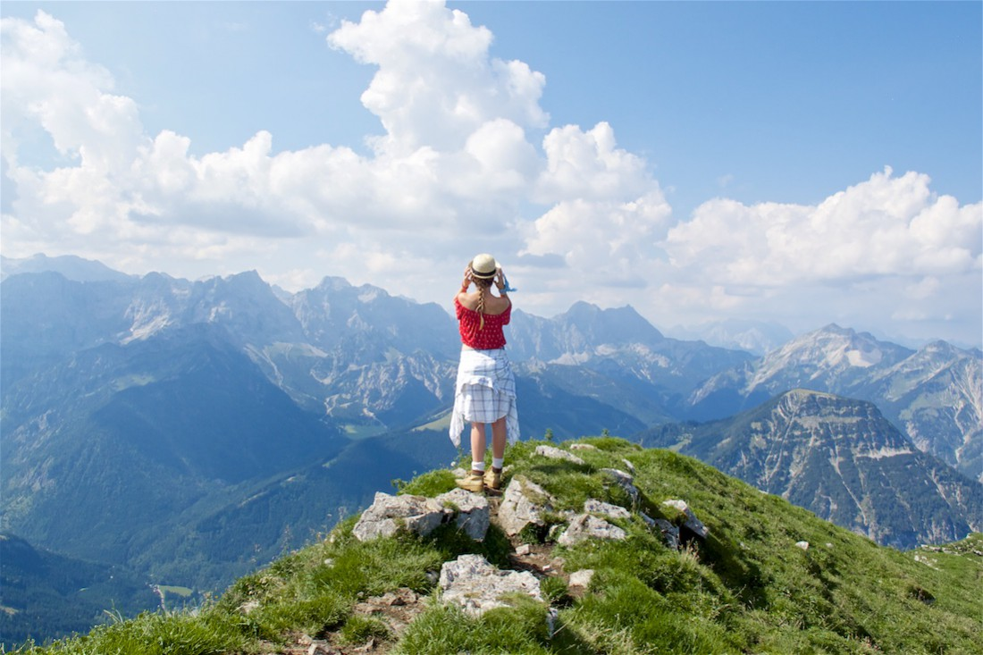 Hiking Day. Fashion Blogger Girl by Style Blog Heartfelt Hunt. Girl with blond dutch braid wearing a red off-shoulder top, plaid shirt, denim shorts, hiking boots and straw hat.