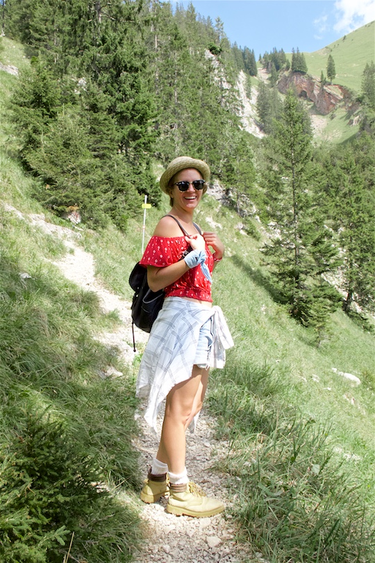 Hiking Day. Fashion and Style Blog Girl from Heartfelt Hunt. Girl with blonde dutch braid wearing a red off-shoulder top, plaid shirt, denim shorts, hiking boots, straw hat, backpack and Ray-Ban sunglasses.