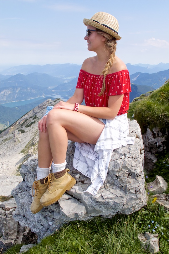Hiking Day. Fashion and Style Blog Girl from Heartfelt Hunt. Girl with blonde dutch braid wearing a red off-shoulder top, plaid shirt, denim shorts, hiking boots, straw hat and Ray-Ban sunglasses.