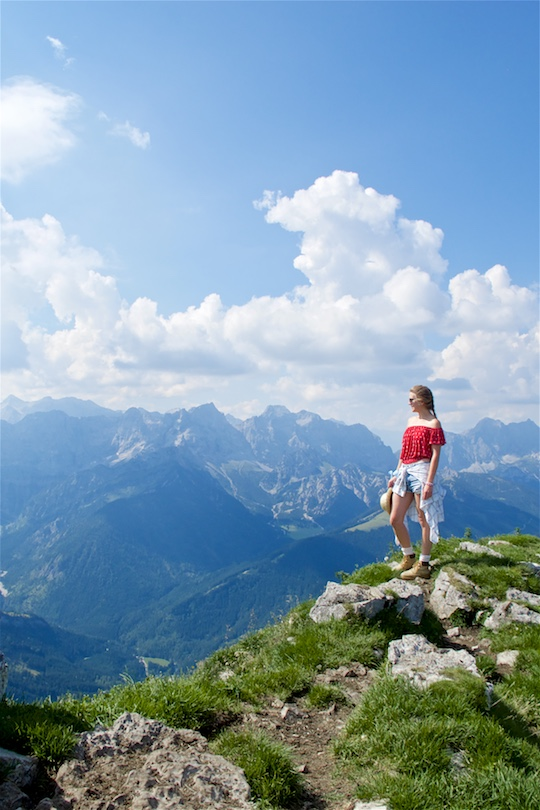 Hiking Day. Fashion Blogger Girl by Style Blog Heartfelt Hunt. Girl with blond dutch braid wearing a red off-shoulder top, plaid shirt, denim shorts, hiking boots, straw hat and Ray-Ban sunglasses.