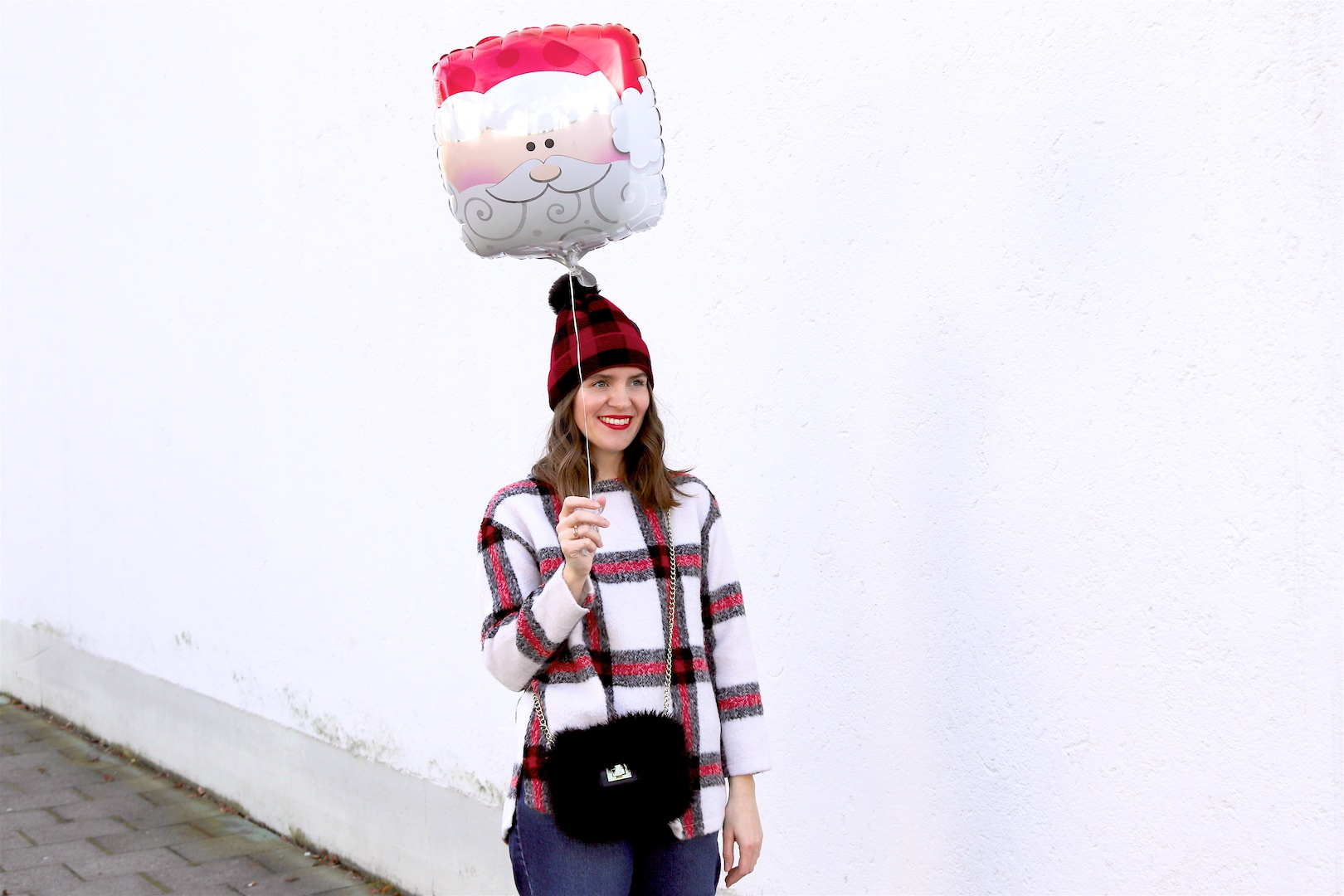 Holiday Season Gear. Fashion Blogger Girl by Style Blog Heartfelt Hunt. Girl with blond, loose curls wearing a plaid beanie, plaid sweater, wide leg jeans, faux fur bag and glossy boots.