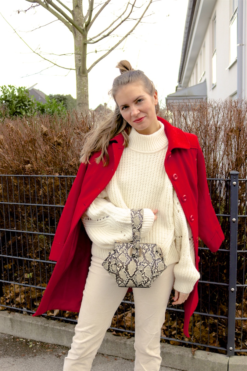 Holiday Season Whites. Fashion and Style Blog Girl from Heartfelt Hunt. Girl with blonde half-up half-down messy bun wearing an off-white chunky sweater, off-white corduroy pants, red coat, snake print bag and black sock boots.