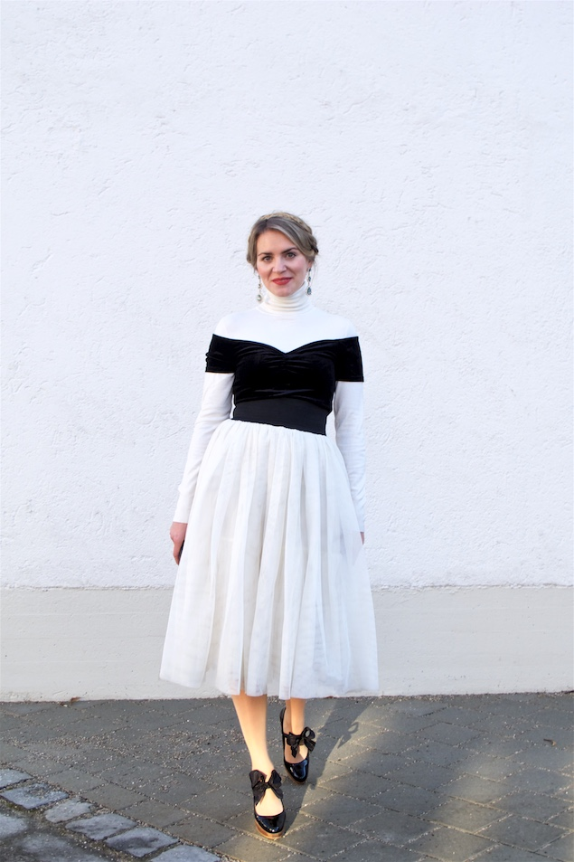 Holiday Tulle Styles. Fashion and Style Blog Girl from Heartfelt Hunt. Girl with blonde halo braid wearing a tulle skirt, turtleneck, velvet off-shoulder top, clutch and heels with bows.