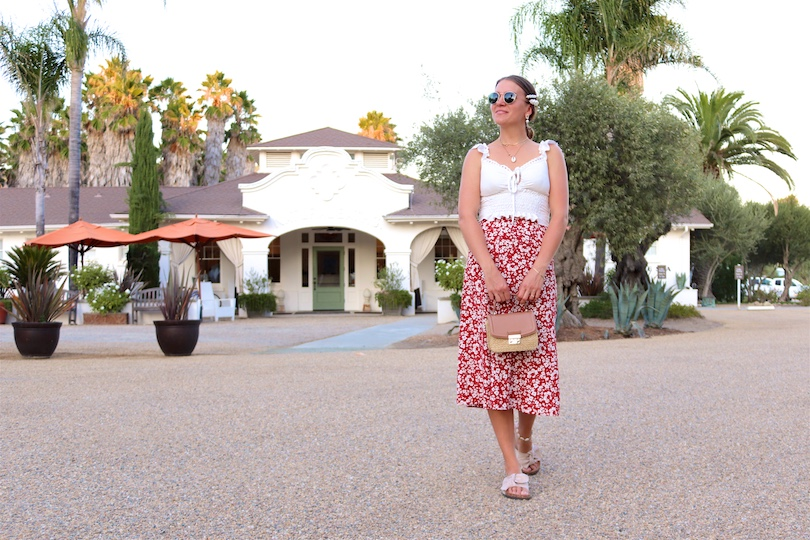 Indian Springs. Fashion Blogger Girl by Style Blog Heartfelt Hunt. Girl with blond, low bun and pearl hair clip wearing Ray-Ban sunglasses, top with ruffles, floral skirt, straw bag and sandals with bow.