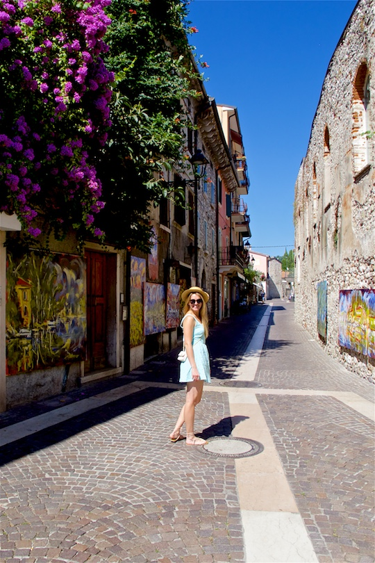 Italian Road Trip. Fashion Blogger Girl by Style Blog Heartfelt Hunt. Girl with long, blond hair wearing a lace dress, straw hat, vintage Chanel bag, sandals and sunglasses.