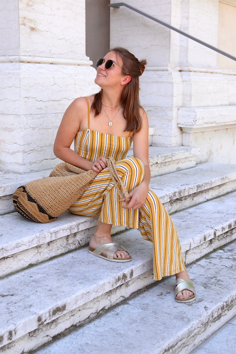 Kids First Aid Travel Kit. Fashion and Style Blog Girl from Heartfelt Hunt. Girl with blonde hair wearing a yellow, striped overall, Ray-Ban sunglasses, woven straw bag and golden sandals showing kids' first aid travel kit.
