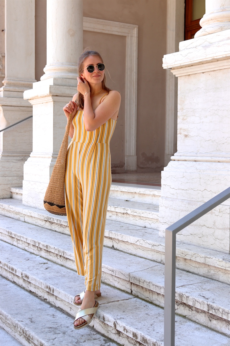 Kids First Aid Travel Kit. Fashion Blogger Girl by Style Blog Heartfelt Hunt. Girl with blond hair wearing a yellow, striped overall, Ray-Ban sunglasses, woven straw bag and golden sandals showing kids' first aid travel kit.