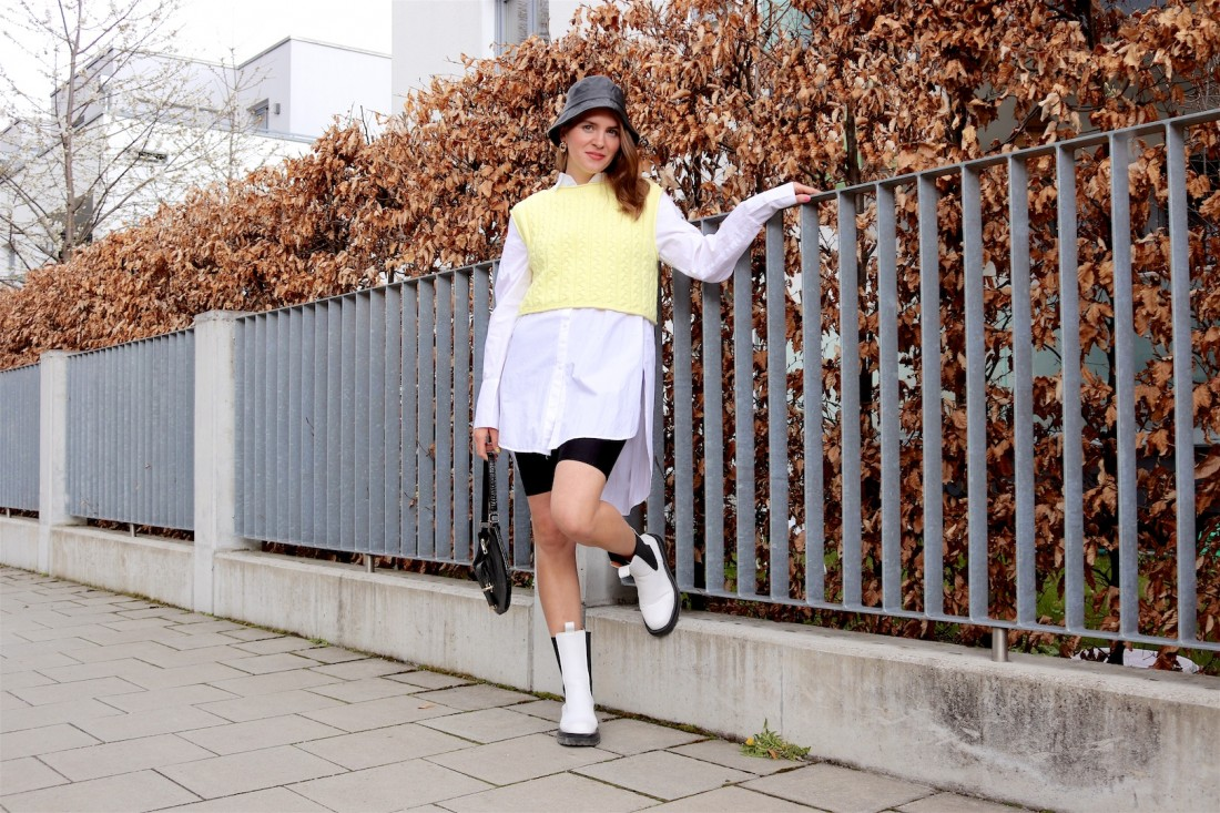 Knitted Vest. Fashion Blogger Girl by Style Blog Heartfelt Hunt. Girl with blond hair wearing a knitted vest, long blouse, faux leather bucket hat, cycling shorts, 90s bag and white boots.