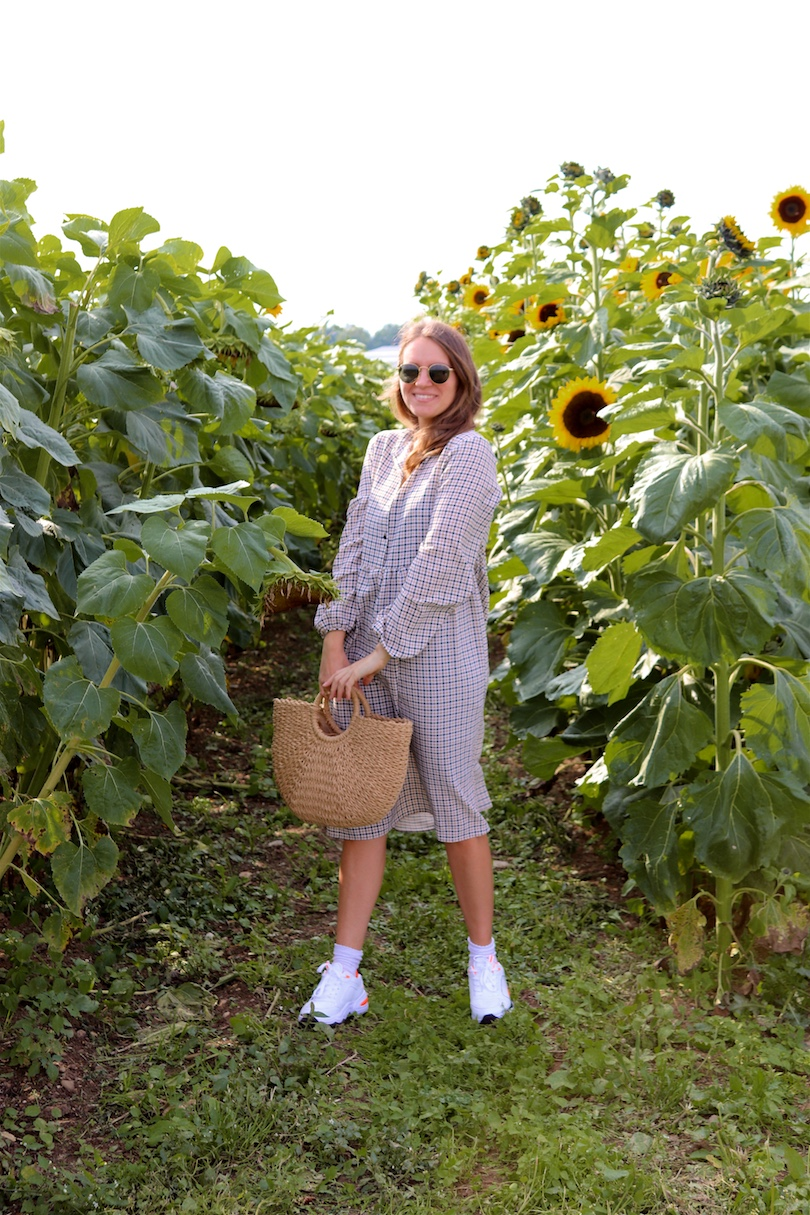 Late Summer Vibes. Fashion Blogger Girl by Style Blog Heartfelt Hunt. Girl with blond loose waves and tortoiseshell hair clips wearing a checked dress, Ray-Ban sunglasses, straw bag and chunky sneakers.