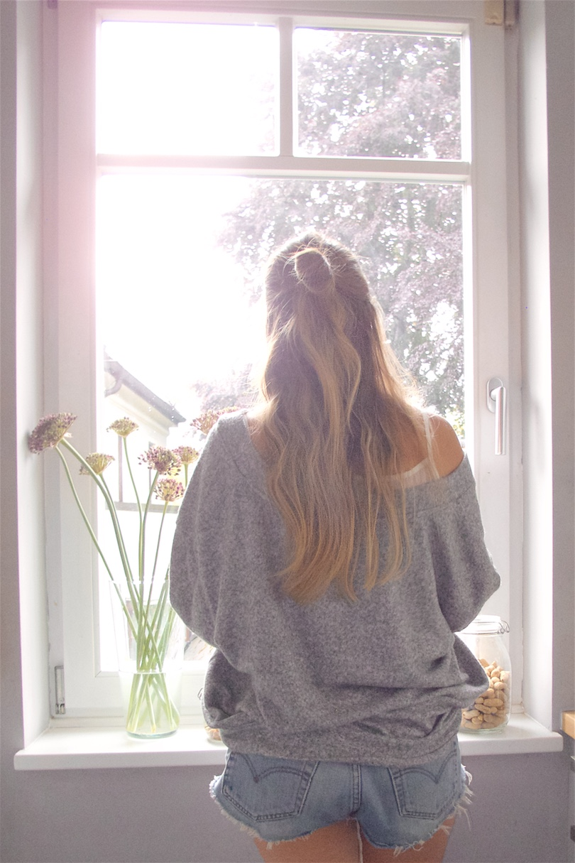 Lazy Days. Fashion Blogger Girl by Style Blog Heartfelt Hunt. Girl with blond, long hair and half-up half-down bun wearing a sweater, top and denim shorts.